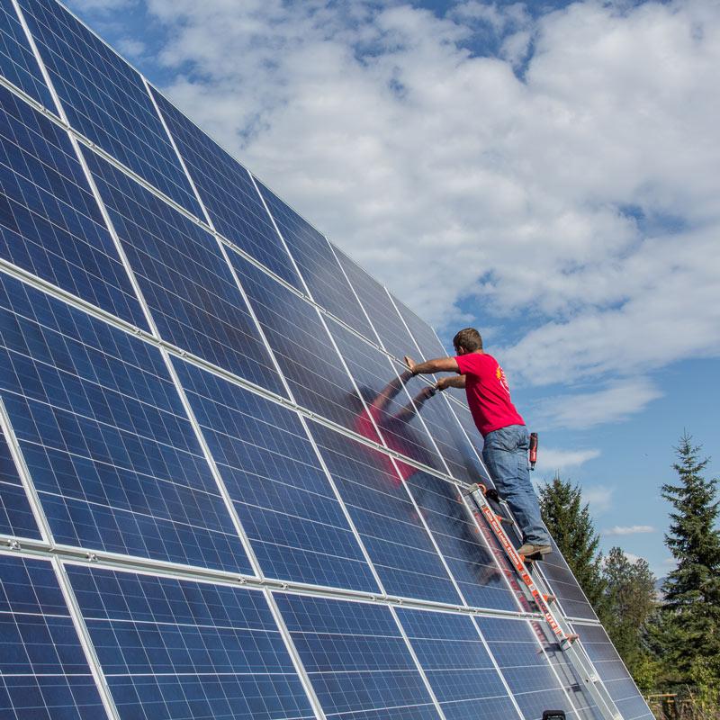 travis jordan working on large solar energy array hamilton montana